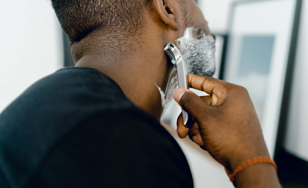 man shaving using a razor