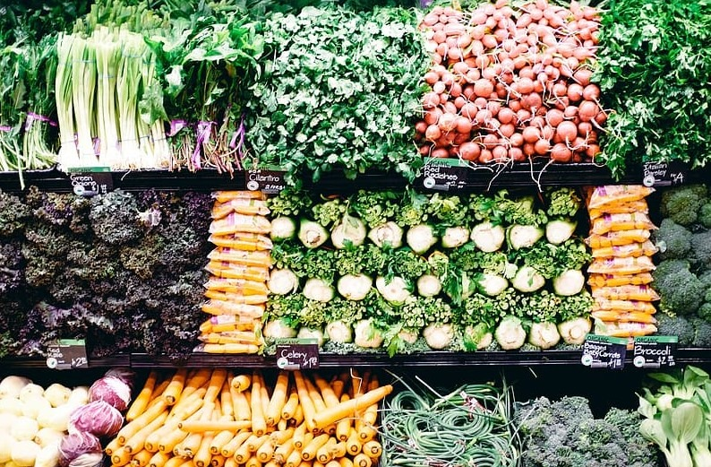 Neatly stacked vegetables in a supermarket aisle